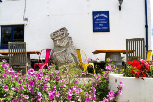 Colourful chairs and stone-carved dinosaur outside the Square and Compass museum, Worth Matravers