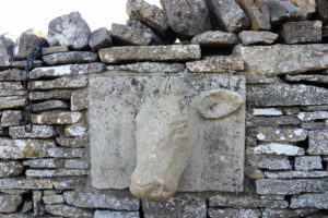 Cow carving set into dry stone wall at Dancing Ledge