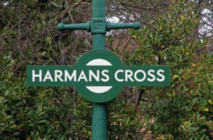 Green and white sign Harman's Cross station