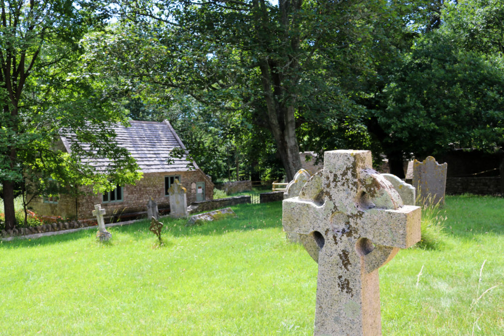 Headstone at Tyneham with schoolhouse in background