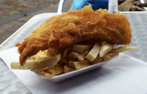 Battered cod on top of chips in takeaway tray