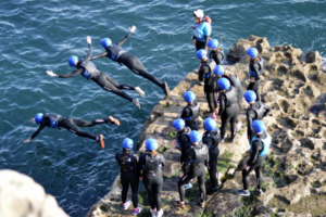 People in wetsuits and helmets jumping into the sea