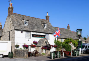 British flag and hanging baskets outside the Castle Inn pub in Corfe Castle
