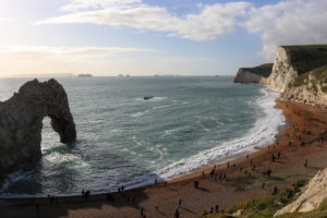 The beach at Durdle Door with people walking