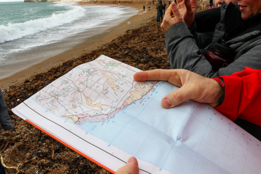 Person looking at map on Durdle Door beach