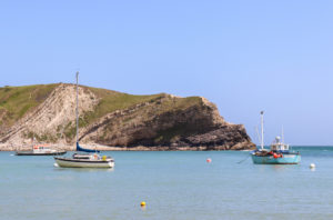 Fishing boats in the cove at Lulworth with strata in cliff behind