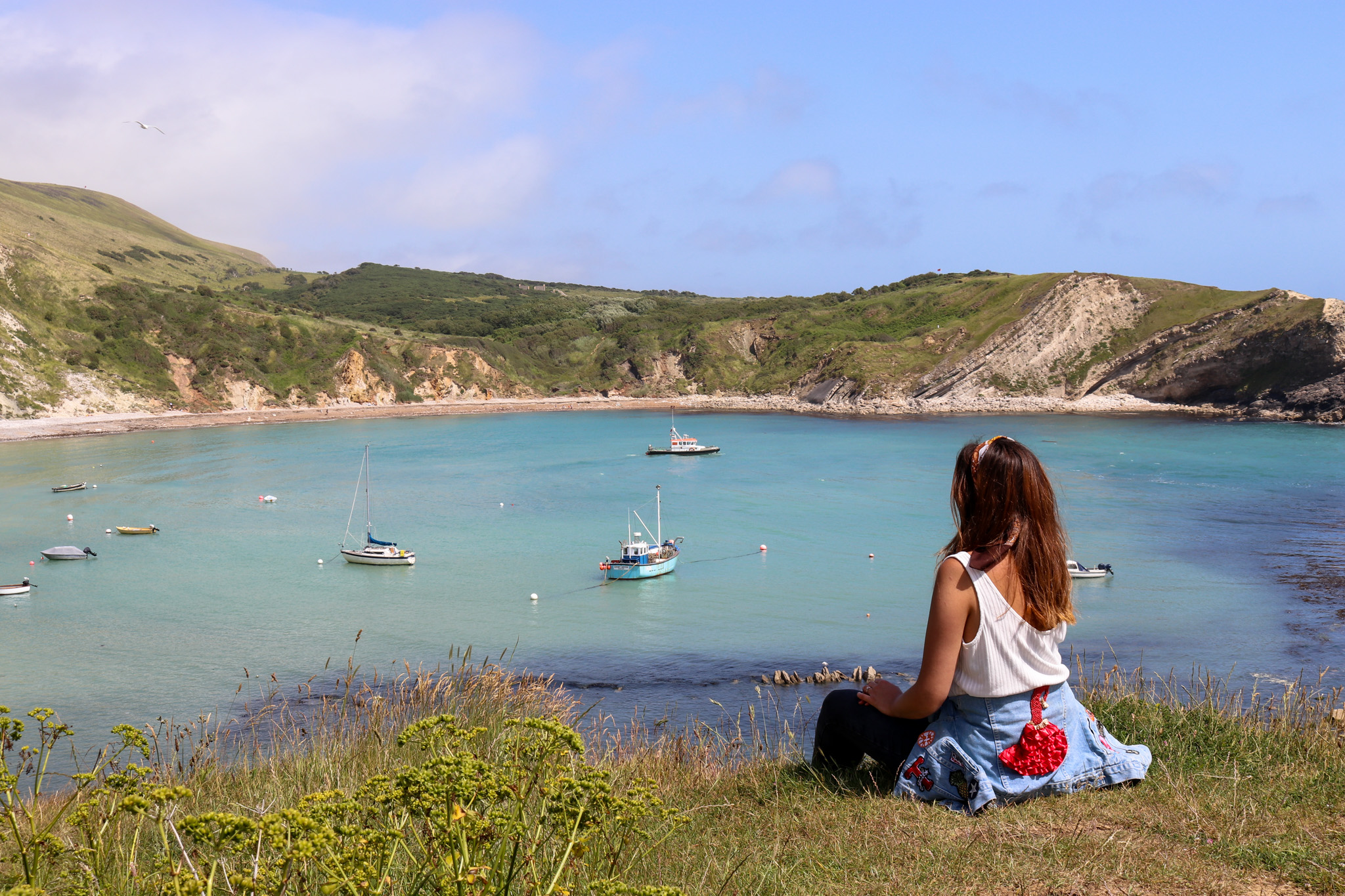 Woman in white top sitting on the cliff above Lulworth Cove looking at the view