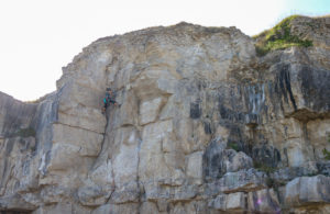 Person rock climbing on the cliff at Winspit