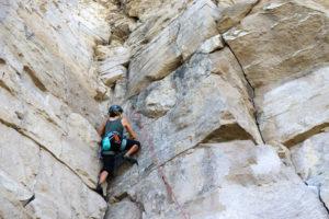 Rock climber adjusting ropes at Winspit