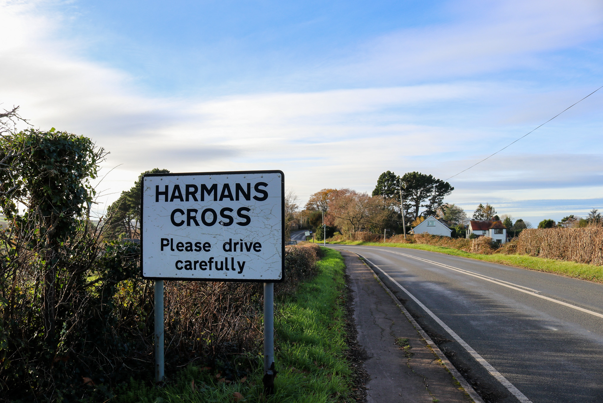 Sign on the road at the entrance to Harman's Cross village
