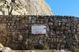 Keep Out warning sign on stone wall at Durlston's Tilly Whim Caves