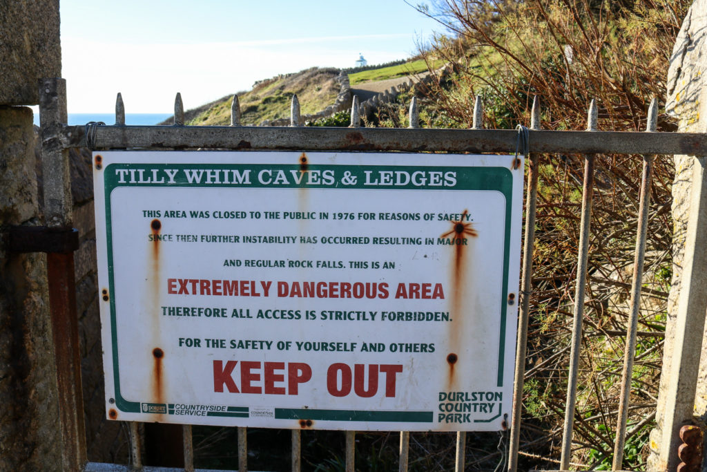 Entrance to Tilly Whim Caves with dangerous area sign at Durlston