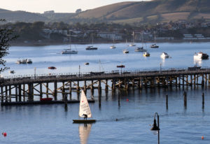 Person sailing past Swanage Pier