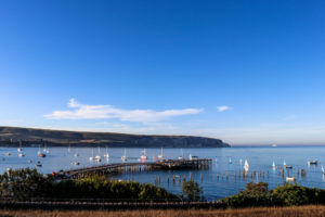 Both new and old piers in Swanage, with sailing boats in the bay