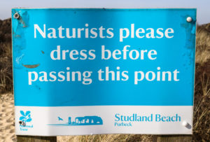 Sign reminding naturists to dress when leaving Studland Naturist Beach