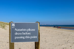 Sign on Studland Naturist beach asking people to dress past this point