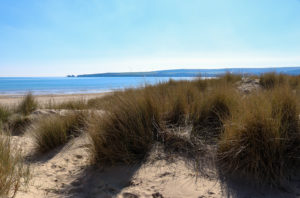 Sand dunes at Studland Naturist Beach, looking across the sea to Old Harry Rocks