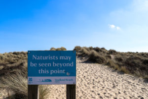 Naturists May Be Seen sign in the dunes leading to Studland Naturist Beach
