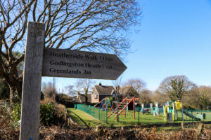 Wooden sign for Godlingston Heath outside Studland village playground
