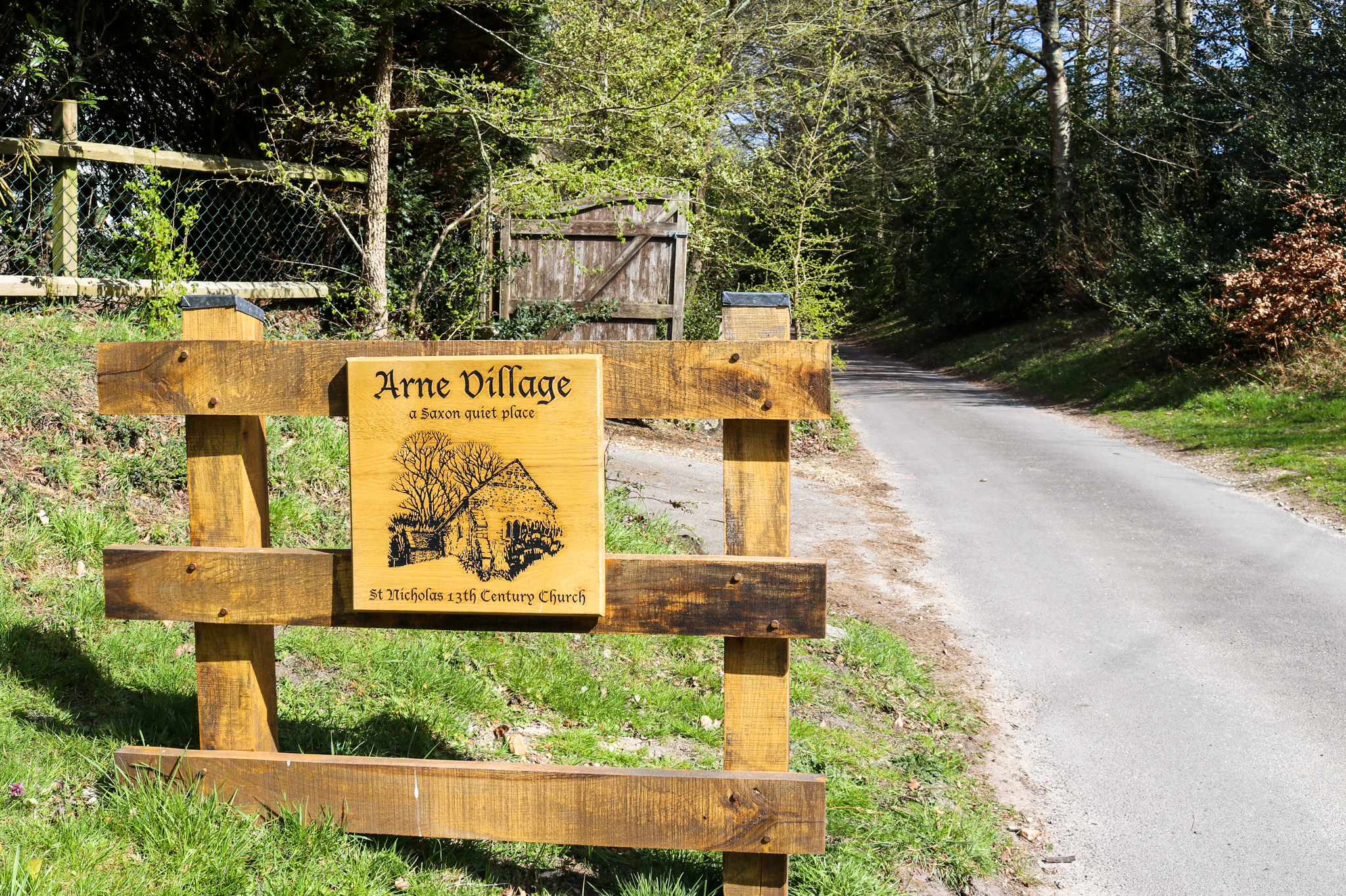 Wooden sign for Arne Village a Saxon quiet place