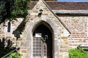 Entranceway with wreath on door of St Nicholas' Church in Arne