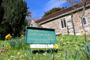 Sign on the lawn of St Nicholas' Church in Arne