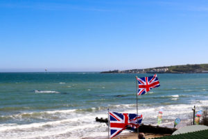 British flags flying on Swanage beach outside The Cabin café