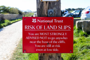 Risk of land slips National Trust sign at Spyway car park for Dancing Ledge