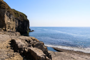 Couple sitting on rocks looking out at the sea at Dancing Ledge
