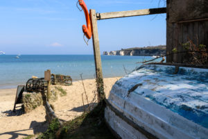 Boat, life vest and lobster pots at South Beach, Studland