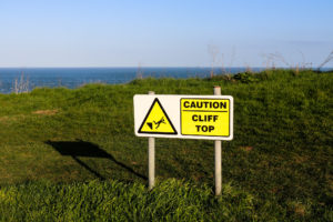 Precarious cliff caution sign in Swanage up at The Downs