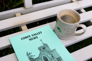 Copy of the Corfe Valley News on a white bench