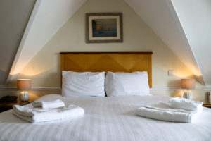 Folded towels on freshly made bed at the Grand Hotel in Swanage