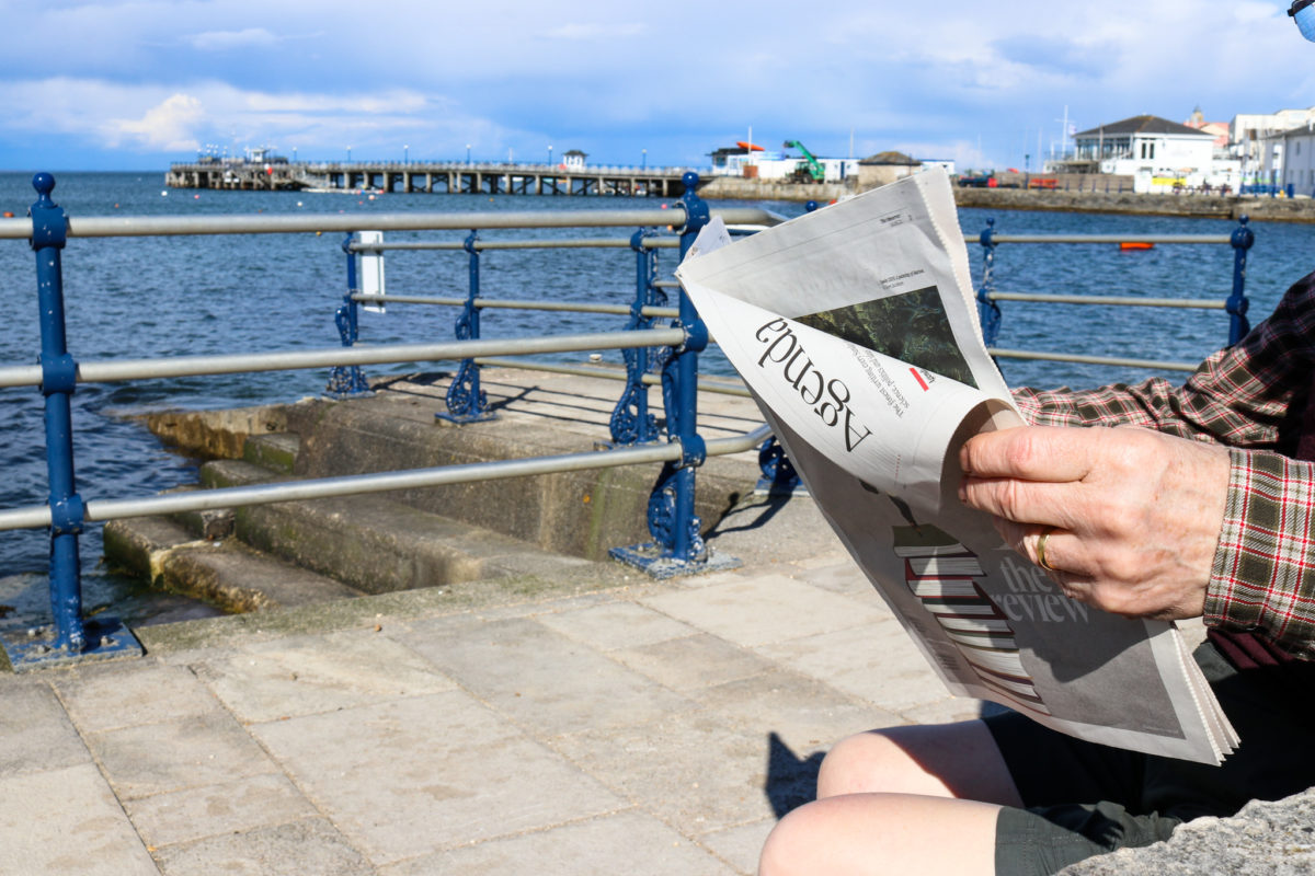 Man reading a newspaper with Swanage Pier in the background