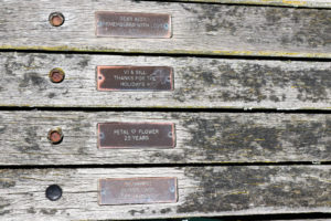 Celebratory and memorial plaques on the planks of Swanage Pier