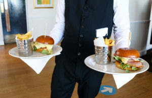 Waiter holding two plates of brie and bacon burgers at the Grand Hotel, Swanage