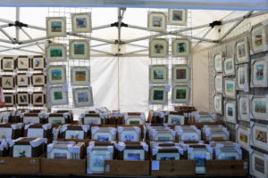 Picture framer and UK artists' work for sale at a festival in Swanage