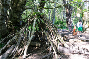 Girl exploring by a den in Durlston woods