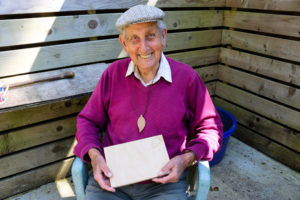 Man holding whittled work of leaf and mouse cheese board at Durlston Country Park
