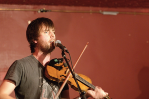 Musician Jon Boden playing the fiddle and singing