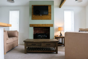 Coffee table, fire and TV on wall in living area of Swanage Coastal Park holiday home