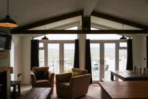 View of Purbeck Hills through double French doors of Swanage Coastal Park caravan