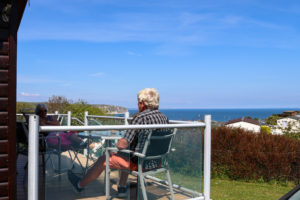 People sitting on the deck of a holiday home at Swanage Coastal Park