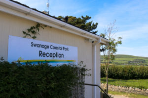 Reception sign at Swanage Coastal Park with Purbeck Hills in background
