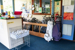 Golf balls and clubs in the reception area of Swanage Golf Games