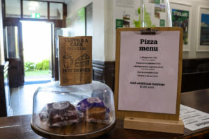 Muffins for sale and pizza menu at Swanage Youth Hostel