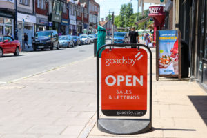 'Open' sign outside estate agents Goadsby, Swanage