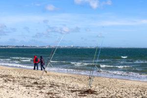 People walking along beach past fishing rods