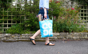 Woman walking down the road with a Swanage Co Op carrier bag