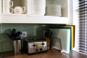 Plates, cups, chopping boards, toaster and utensils in Swanage YHA self-catering kitchen